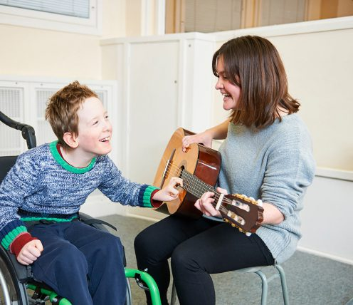 Nordoff Robbins music therapist and beneficiary with guitar
