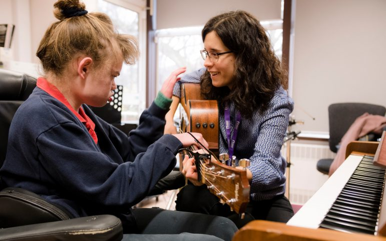 Nordoff Robbins music therapist and beneficiary with guitar and piano