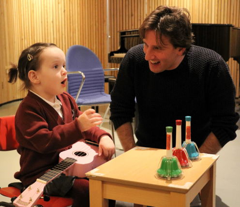 Girl and music therapist playing instruments at Nordoff Robbins London Centre