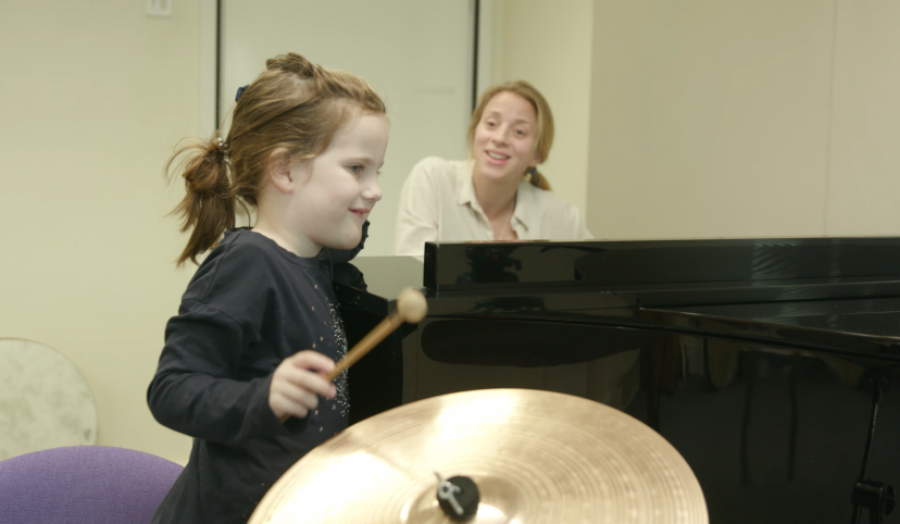 Nordoff Robbins music therapist and girl playing cymbals