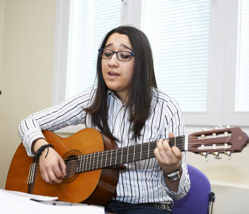 Young lady playing the guitar and singing