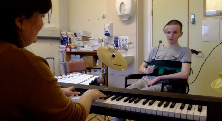 Boy playing drum with music therapist