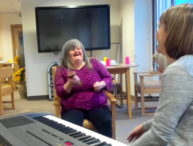 Lady singing with music therapist in supported living