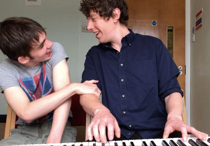 Boy and music therapist playing the piano