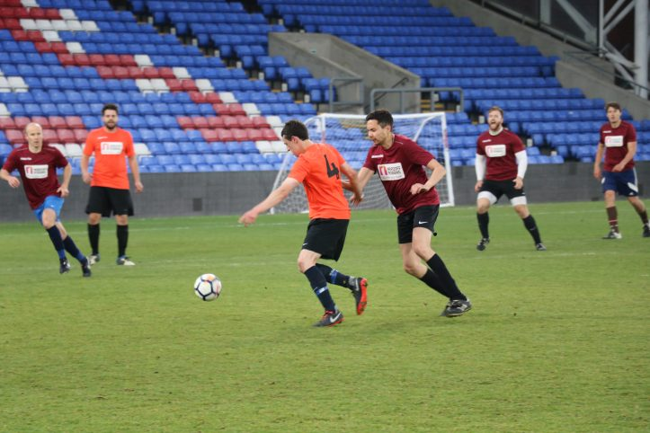 Two male football players, one in an orange kit the other in a maroon kit chase after a football