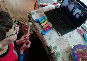 Oscar is looking at a laptop screen showing Afra a music therapist whilst holding a baton above a mini xylophone