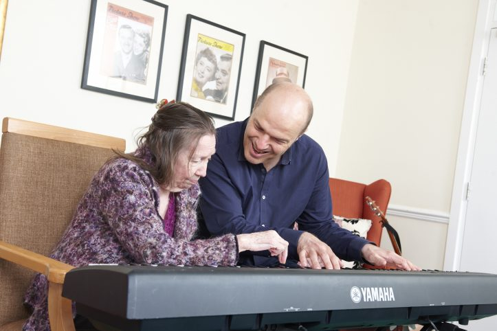 An elderly woman plays keyboards with a smiling male music therapist