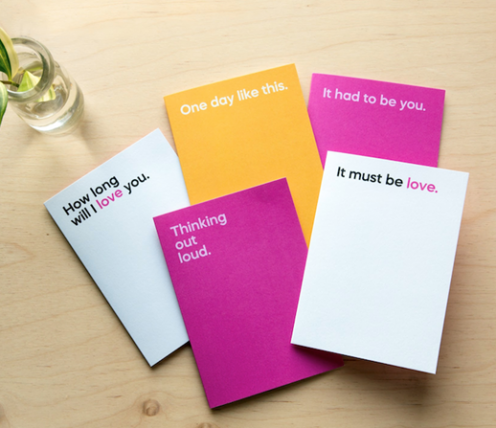 Flat lay of 'Say it With Songs' greeting cards in pink, yellow and white