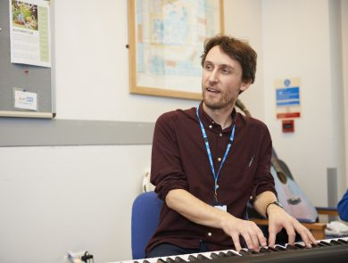 A photo of music therapist John Wallis playing a keyboard and singing