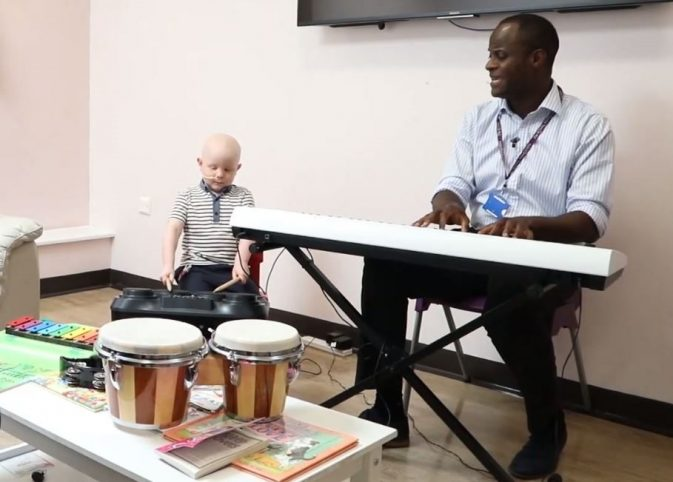 Zachary sits on the floor playing the drums while music therapist Kawku plays an electric keyboard