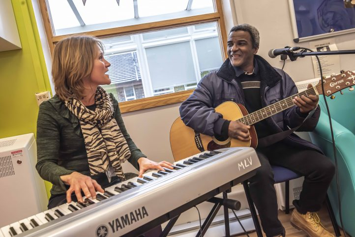 Music therapist Kat is sat playing an electric keyboard and next to her is Bevin playing an acoustic guitar.