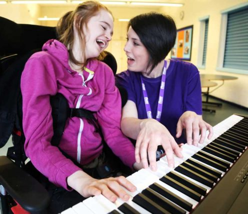 Gird with music therapist at piano