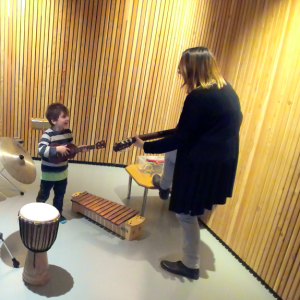 Levi, a young boy holds a guitar facing music therapist Hannah in a music therapy room with a drum and xylophone on the floor