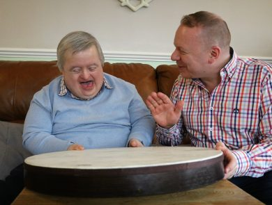 Robert, who has Downs Syndrome and is in his 50s, is sitting next to music therapist Alan making music together