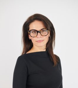 Sandra Schembri is wearing black, standing facing the camera wearing glasses.