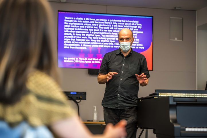 A Nordoff Robbins male music therapist is standing in front of a educational presentation in a learning environment